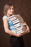 Young girl is holding a pile of books Royalty Free Stock Photography
