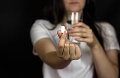 Young girl holding a pill in her hand and a glass of water, close-up. Black background stock photos