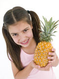 Young girl holding pineapple Stock Images