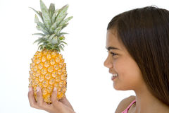 Young girl holding pineapple and smiling Royalty Free Stock Photo