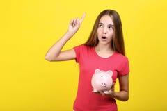 Girl holding pink piggybank stock image