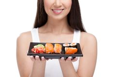 Young girl holding plate of sushi and smiling Royalty Free Stock Photography