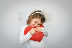 Young girl holding a plush red heart Stock Photo