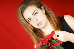 Young girl holding a Poinsettia. Portrait of a beautiful young girl holding a red Poinsettia over red background Royalty Free Stock Image
