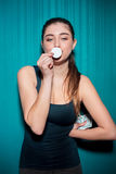 Young girl holding poker chips on blue background Royalty Free Stock Photography
