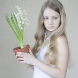 Young girl holding a pot of flowers Stock Photo