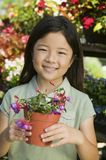 Young girl holding potted flowers in plant nursery portrait Stock Images