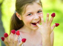 Young girl is holding raspberries on her fingers. Outdoor shoot Stock Photo