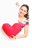Young girl holding a red heart behind blank panel Royalty Free Stock Photo