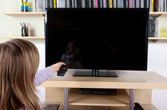 Young girl holding remote control in front of the TV Stock Photos