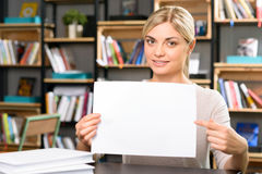 Young girl is holding a sheet of paper Royalty Free Stock Photography