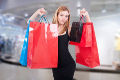 Young girl holding shopping bags up. Inside the mall as fashion and consumerism concept Stock Photos
