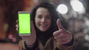 Young girl is holding smartphone with green screen and thumb up at evening time. Casual lifestyle stock footage