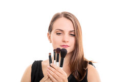 Young girl holding some make-up brushes Royalty Free Stock Photos
