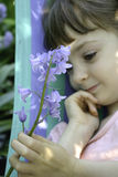 A young girl holding a stem of bluebell flowers Royalty Free Stock Image