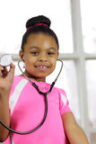 I am interested in a medical career. Young girl holding stethoscope wants to enter the medical career field. Focus on girls eyes Royalty Free Stock Images