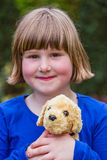 Young girl holding stuffed dog Stock Image