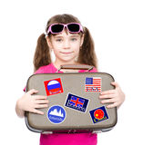 Young girl holding suitcase with stickers from various countries. isolated on white.  Royalty Free Stock Images