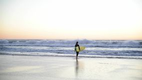 Young girl holding surfboard on the beach. Woman walking with surf into the ocean. Beautiful sunset, wind is blowing.