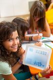 Young girl holding tablet with schoolwork. Stock Photography