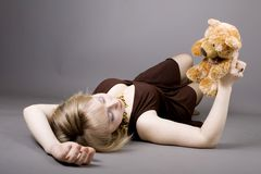 Young girl holding teddy bear. Beautiful young blond girl holding teddy bear royalty free stock photography