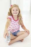 Young Girl Holding Television Remote Control In Bedroom Royalty Free Stock Image