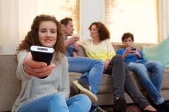 Young girl holding television remote control Royalty Free Stock Photography