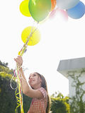 Young Girl Holding Up Balloons In Lawn Stock Photo