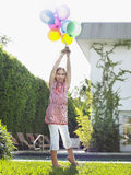 Young Girl Holding Up Balloons In Lawn Royalty Free Stock Photography