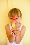 Young girl holding up popsicle Royalty Free Stock Images
