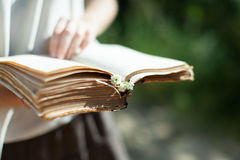 A young girl is holding a very old shabby book in her hands. Sum Stock Photo
