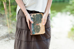 A young girl is holding a very old shabby book in her hands. Sum Stock Photos