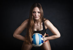 Young girl holding volleyball on black background Royalty Free Stock Photos