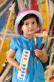 Young Artist. Young girl holding water colors and brushes in front of an abstract painting royalty free stock photo