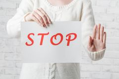Young girl holding a white sign with red inscription STOP on a w. Hite background Royalty Free Stock Images