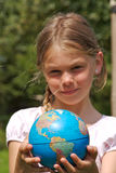 A young girl is holding the world in her hands Stock Images