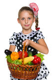Young girl holds a basket with vegetables Stock Images