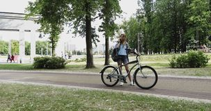 A young girl holds a bicycle and talks to her mobile phone in the park. stock video