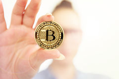 Young girl holds bitcoin in her fingers on background flares Stock Image