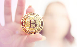 Young girl holds bitcoin in her fingers on background flares Stock Photo