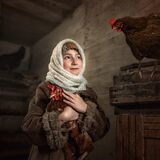 A young girl holds a chicken in her arms and looks at the second one