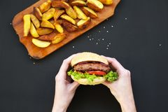 Young girl holds fresh burger. Fried potatoes on wooden board. royalty free stock image