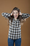 A young girl holds hands behind his head and screams. Royalty Free Stock Photos
