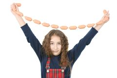 Young girl holds sausages stock photo
