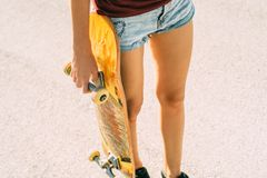 Young girl holds a skateboard in her hand, shorts and a tank top royalty free stock image