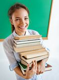 Young girl holds stack of books near blackboard, education concept royalty free stock image