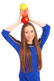 Young girl holds an three apples on her head Royalty Free Stock Image