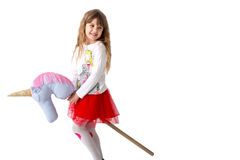 Young girl holds a toy ridge between the legs on a white background. Isolated royalty free stock images
