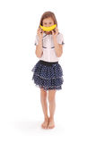 Young girl holds up a banana to her mouth, imitating a smile Royalty Free Stock Photos