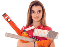 A young girl holds a variety of tools for repairing close-up isolated on white background Royalty Free Stock Photography